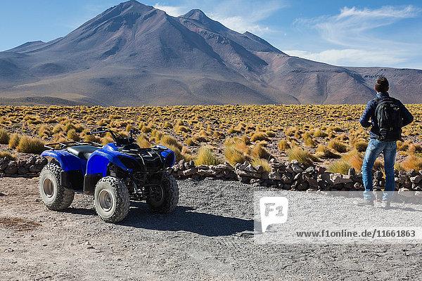 Man by quad bike looking at mountain  San Pedro de Atacama  Chile
