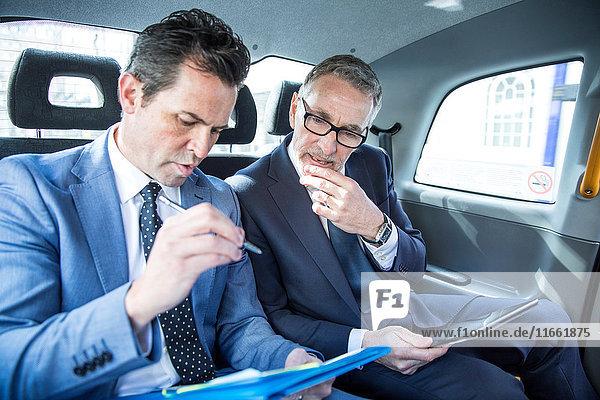 Zwei Geschäftsleute  die sich den Papierkram im Taxi ansehen.