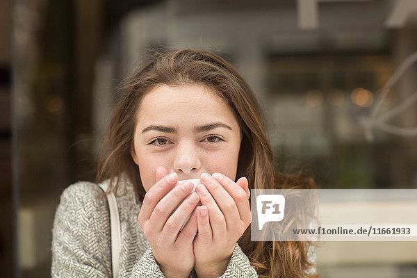 Porträt einer jungen Frau  die in einem Straßencafé Kaffee schöpft