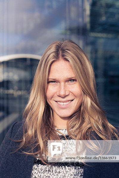 Porträt einer jungen Frau mit langen blonden Haaren vor einem Bürogebäude