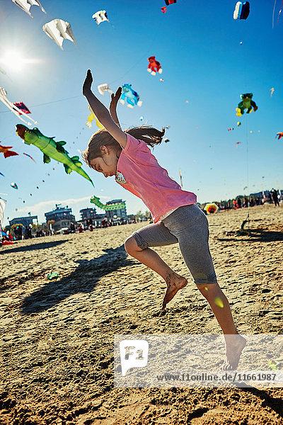 Junges Mädchen beim Radschlagen am Strand  Drachen fliegen im Himmel hinter ihr  Rimini  Italien
