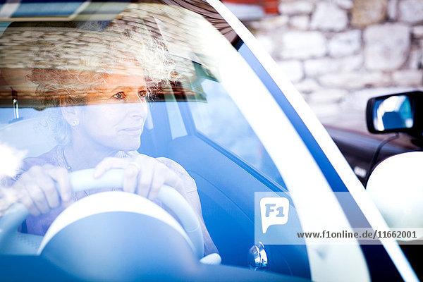 Lächelnde reife Frau schaut durch die Windschutzscheibe eines Autos