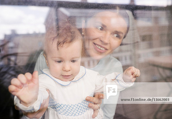 Mutter und Baby schauen durch ein Glasfenster Mutter und Baby schauen durch ein Glasfenster