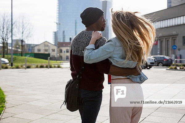 Young couple walking outdoors  arms around each other  rear view