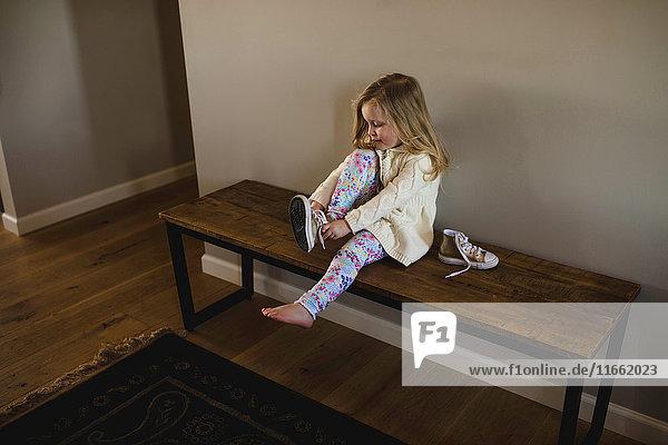 Auf der Bank sitzendes Mädchen zieht Turnschuh an