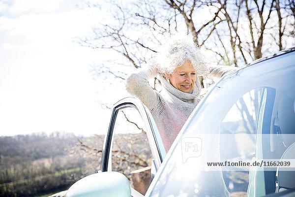 Reife Frau zieht Pullover im Auto am ländlichen Straßenrand an