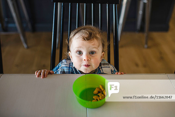 Portrait of blue eyed male toddler looking up from table