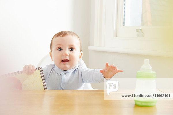 Baby boy on high chair reaching for baby bottle