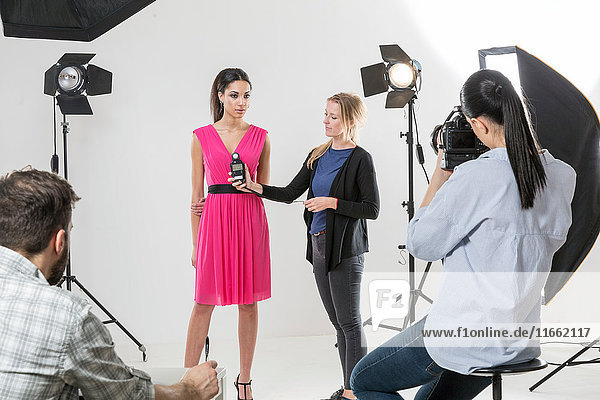 Photographer using light meter in white backdrop photography studio shoot