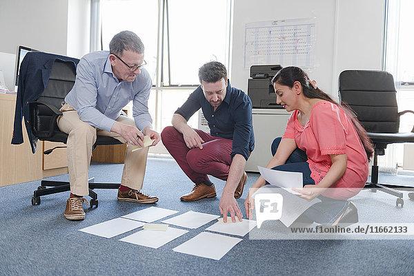 Kollegen diskutieren Papiere im Büro