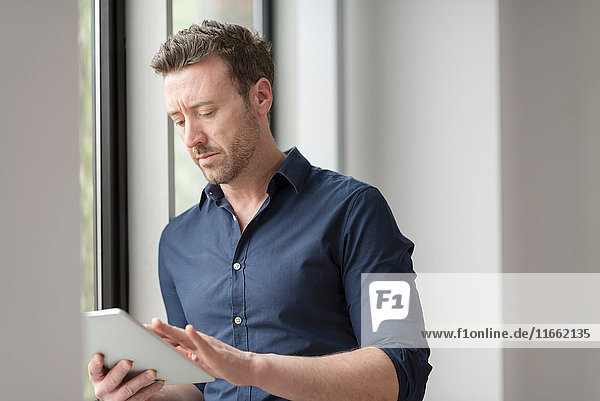 Mann benutzt digitales Tablett durch Bürofenster