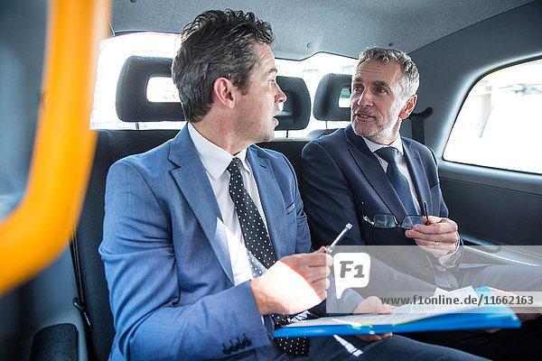 Zwei Geschäftsleute diskutieren über den Papierkram im Taxi
