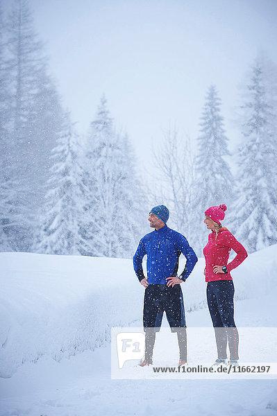 Läuferinnen und Läufer beobachten Schneefall von einer tief verschneiten Loipe  Gstaad  Schweiz