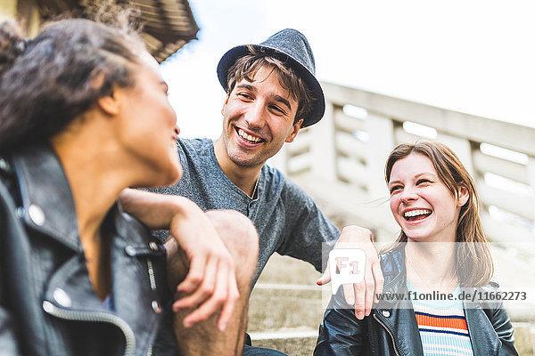 Vier junge erwachsene Freunde auf der Treppe plaudern im Battersea Park