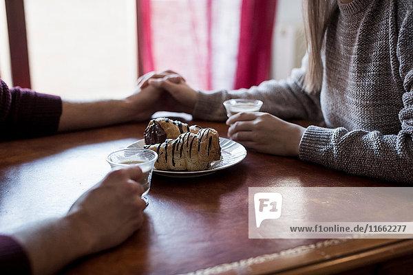 Paar am Tisch sitzend  Hände haltend  Kaffeetassen haltend  Gebäck auf dem Tisch  Nahaufnahme