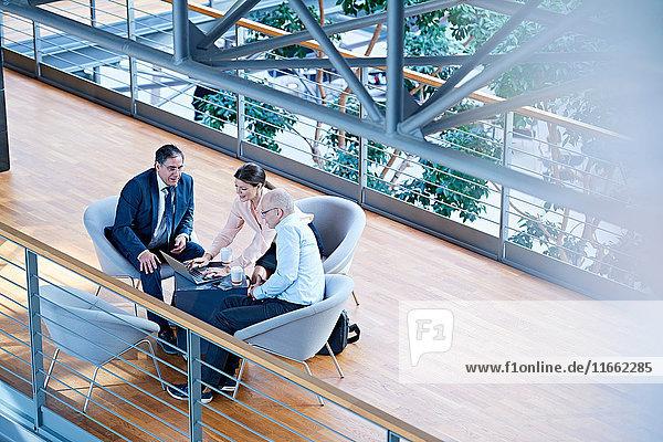 Schrägansicht von Geschäftsleuten  die sich auf dem Balkon des Büros treffen