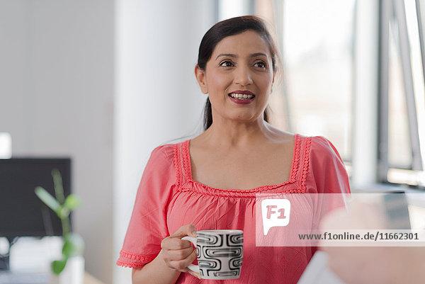 Frau spricht mit Kollegin in Kaffeepause
