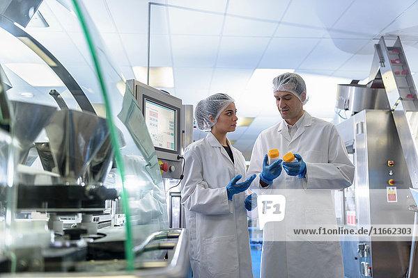 Arbeiter inspizieren Produkt in pharmazeutischer Fabrik