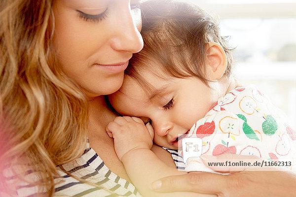 Müdes kleines Mädchen mit Kopf auf den Schultern der Mutter