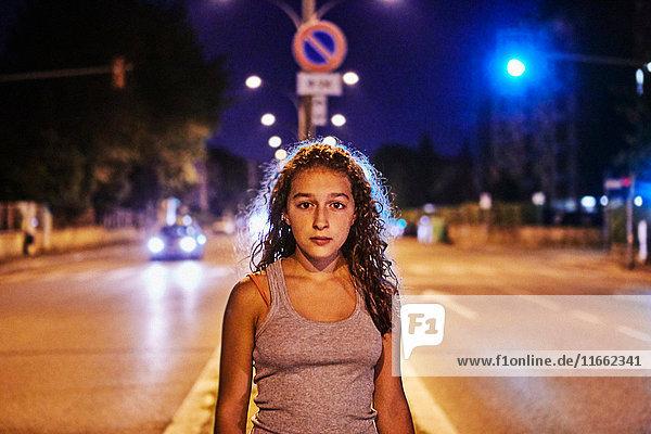 Porträt einer Teenagerin mitten auf der Straße  die in die Kamera schaut