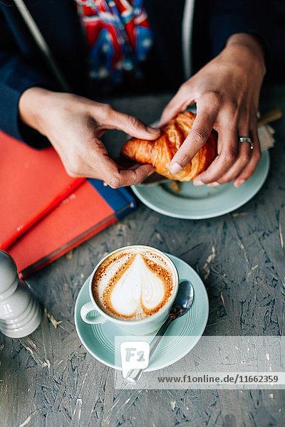 Draufsicht auf die Hand einer Frau  die im Cafe ein Croissant hält