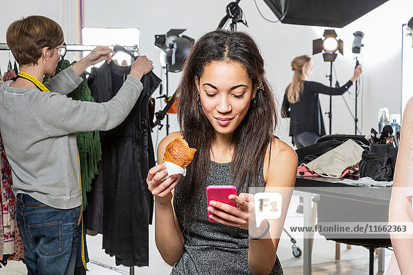 Young female fashion model looking at smartphone in photographers studio