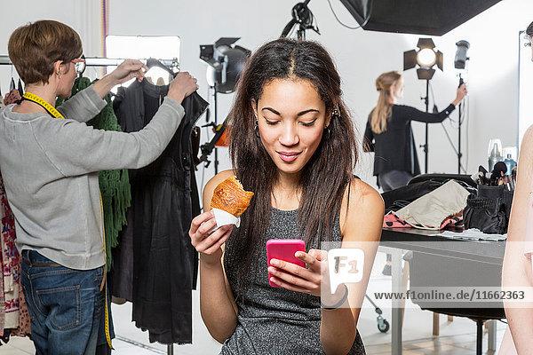 Junges weibliches Modemodel betrachtet Smartphone im Fotografenstudio