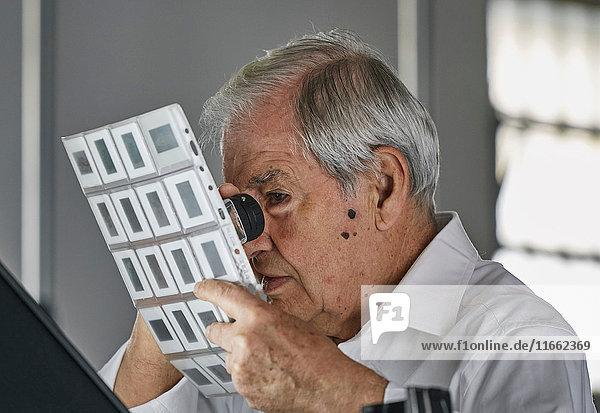 Älterer Mann betrachtet Filmblätter mit einer Lupe