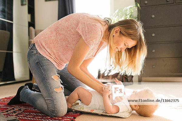 Mutter kitzelt Baby auf Teppich Mutter kitzelt Baby auf Teppich