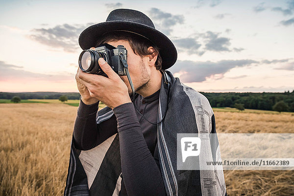 Mid adult man  standing in field  taking photograph with SLR camera  Neulingen  Baden-Württemberg  Germany