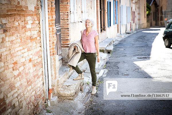 Frau auf der Straße schaut lächelnd weg  Bruniquel  Frankreich