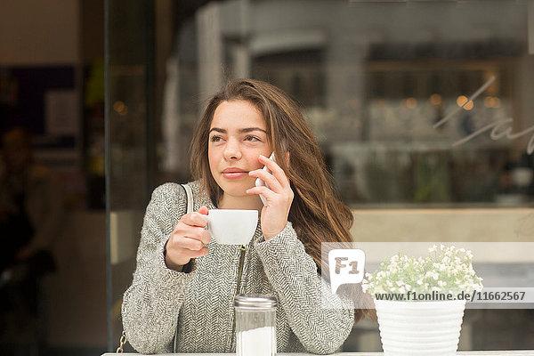 Junge Frau telefoniert mit Smartphone vom Straßencafé aus