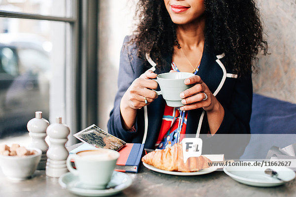Cropped shot of woman holding coffee cup in cafe
