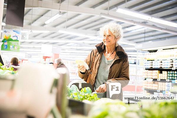 Reife Frau im Supermarkt  die sich frische Produkte ansieht