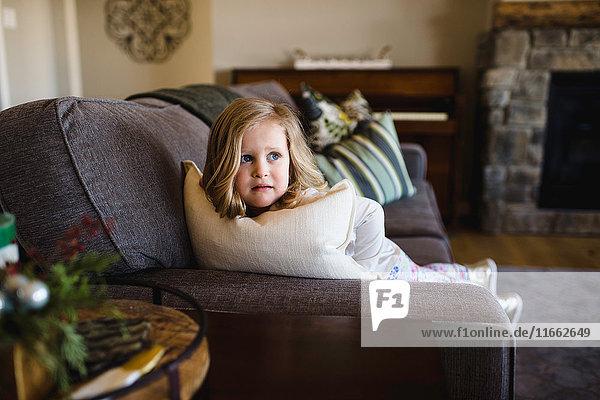 Fearful girl looking sideways from sofa