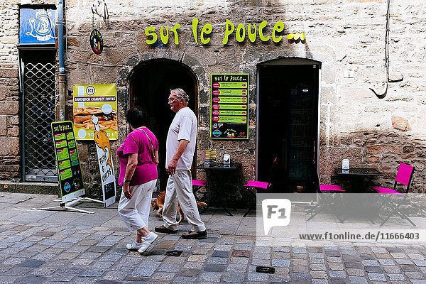 Elder couple with dog walking on the stone streets and passing by a terrace restaurant  Dinan  Côtes-d'Armor  Brittany  France.