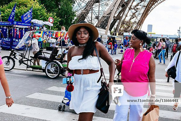 Afro french women walking on street next to Eiffel tower  Paris  Île-de-France  France.