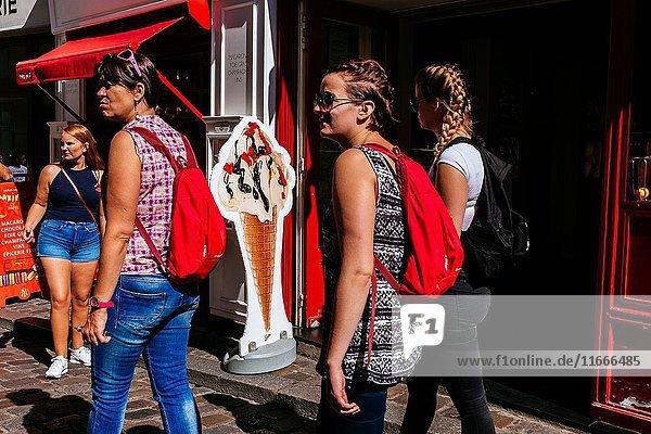 Young tourists women walking down street passing by ice cream shop. Montmartre  Paris  Île-de-France  France