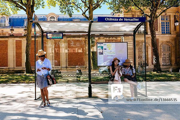 Women sitting at bus stop waiting for bus to come. Versailles  Île-de-France  France.
