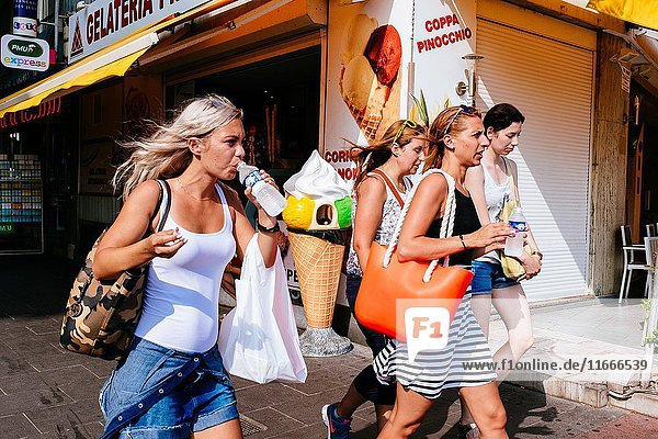 Group of women walking on street  drinking cold water passing by ice cream shop. Nice  Alpes-Maritimes  French Riviera  Provence-Alpes-Côte d'Azur  France.