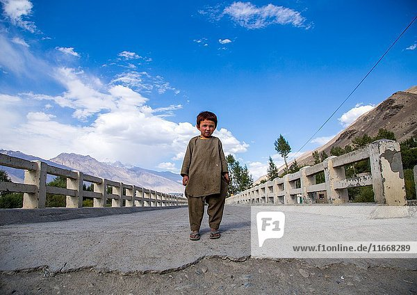 Afghan boy standing in the middle of a bridge  Badakhshan province  Khandood  Afghanistan.