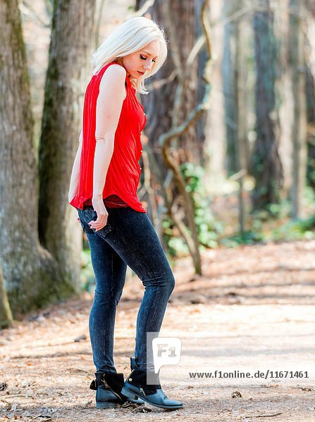 A pretty 30 year old blond woman in casual clothing on a path in a forest.