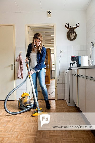 Tilburg  Netherlands. Young caucasian woman dustcleaning the floor of her kitchen.
