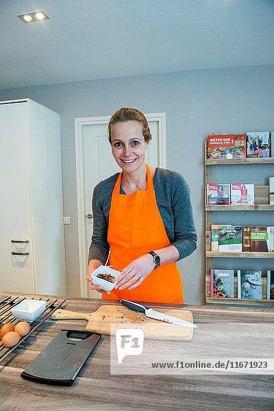 Kaatsheuvel  Netherlands. Mid adult caucasian woman preparing to bake a cake inside her residential kitchen.