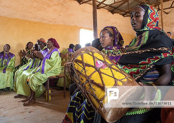 Borana woman playing drum during sunday church service  Oromia  Yabelo  Ethiopia.