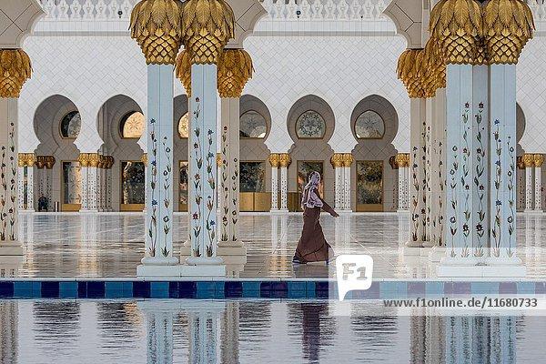 United Arab Emirates - Woman walking in Sheikh Zayed Mosque in Abu Dhabi.