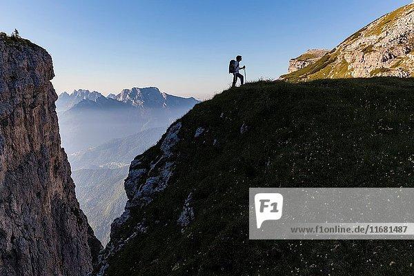 Hiker in silhouette near fork Besausega  Dolomites  Pale di San Lucano  Agordino  Belluno  Veneto  Italy  Europe.
