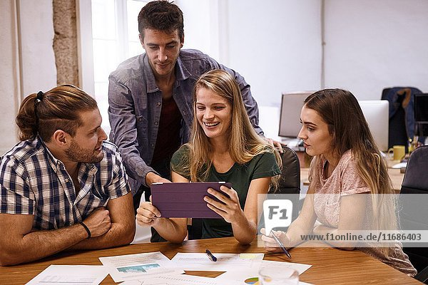 Young professional team with two males and two females planning a fresh new approach for their company to evolve further and better with tablet pc.