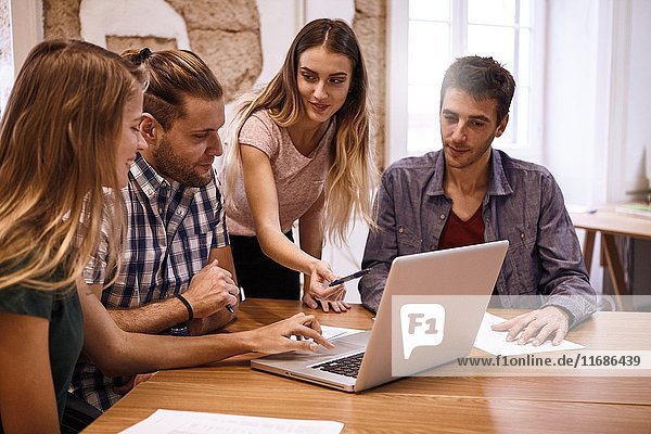 Young business team with two male and two female professionals in a interactive presentational meeting with a laptop pc on the desk between them.