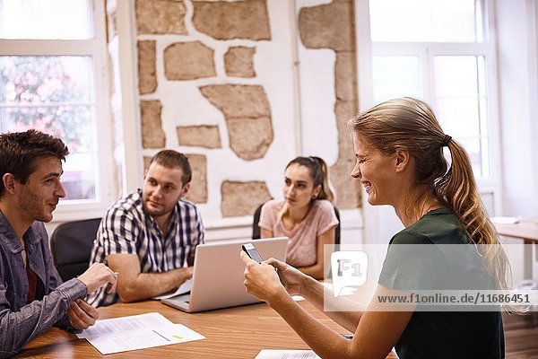 Four young professionals having a business discussion around a table in an office with bright sunlight streaming through the windows.